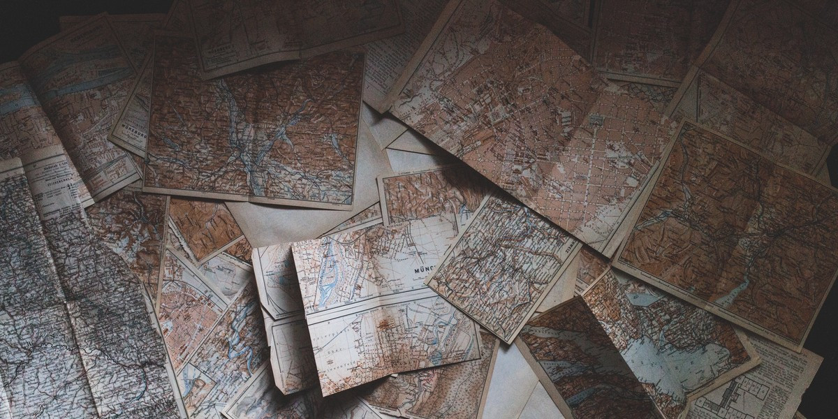A collection of partially unfolded paper maps.